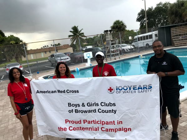 Three Teens and their swim coach standing in front of a pool holding up an American Red Cross Banner for the Centennial Campaign.