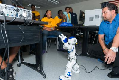 Instructor showing a robot to a classroom of students on career day.