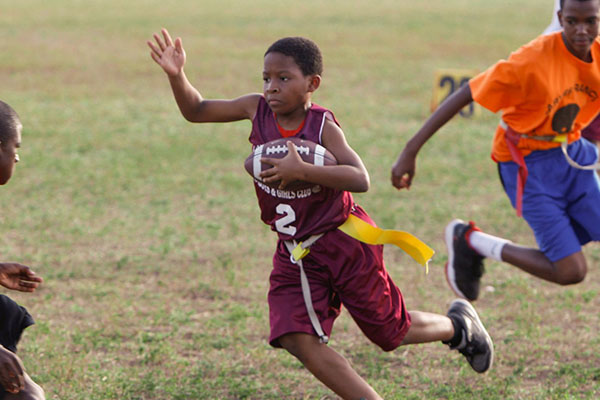 Young boy running with a football in his arms during a game of flag football.
