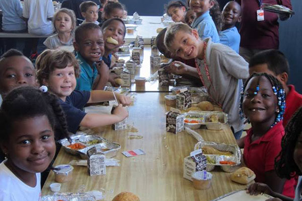 Group of young kids sitting at folding tables eating lunch, smiling and appear to be happy.