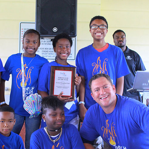 Group of kids from Torch program holding an award plaque.