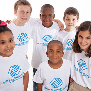 Six kids wearing boys and girls club t-shirts smiling for the camera.